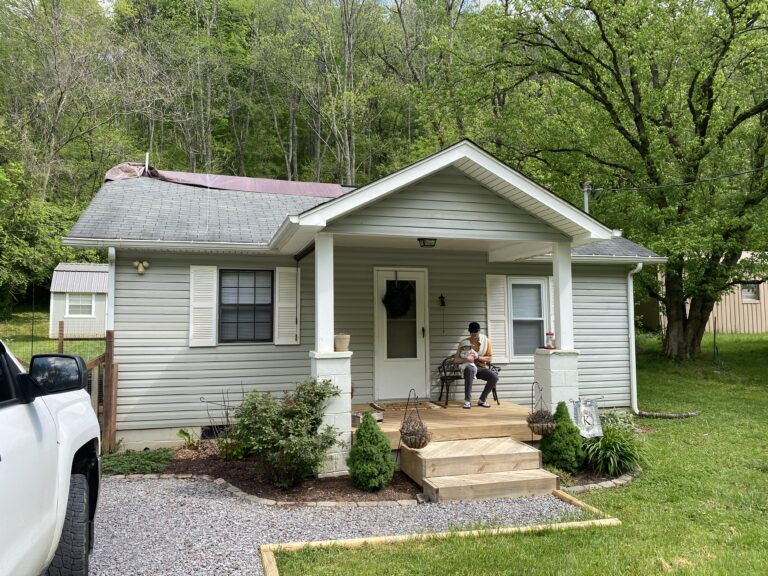 This is a picture of a gray home with an old three tab roof