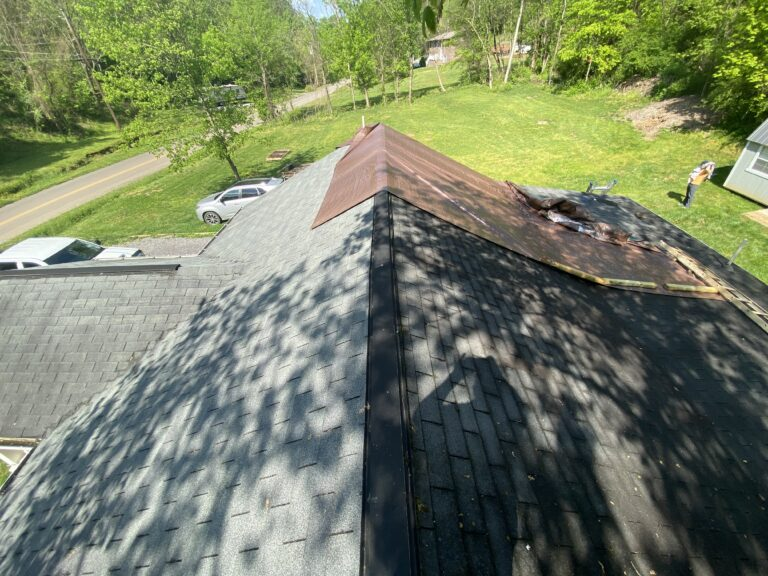 This is a picture of an old gray three tab roof with a brown tarp
