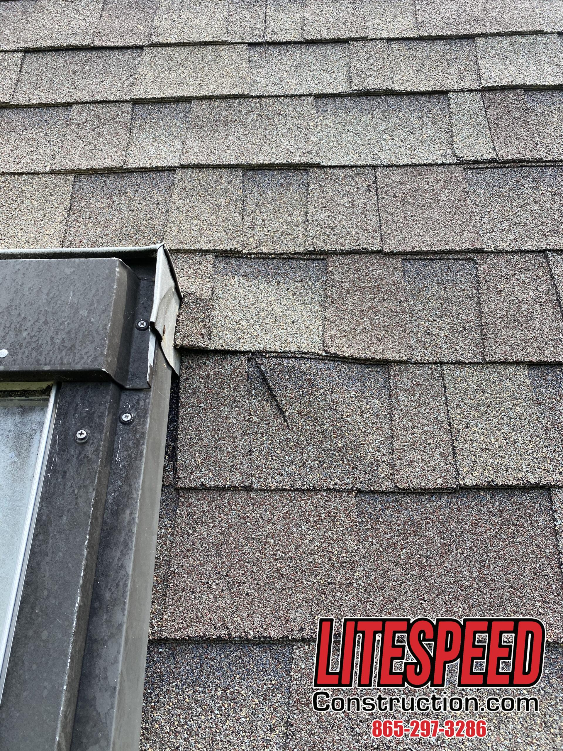 This is a picture of a crack on a shingle next to a skylight
