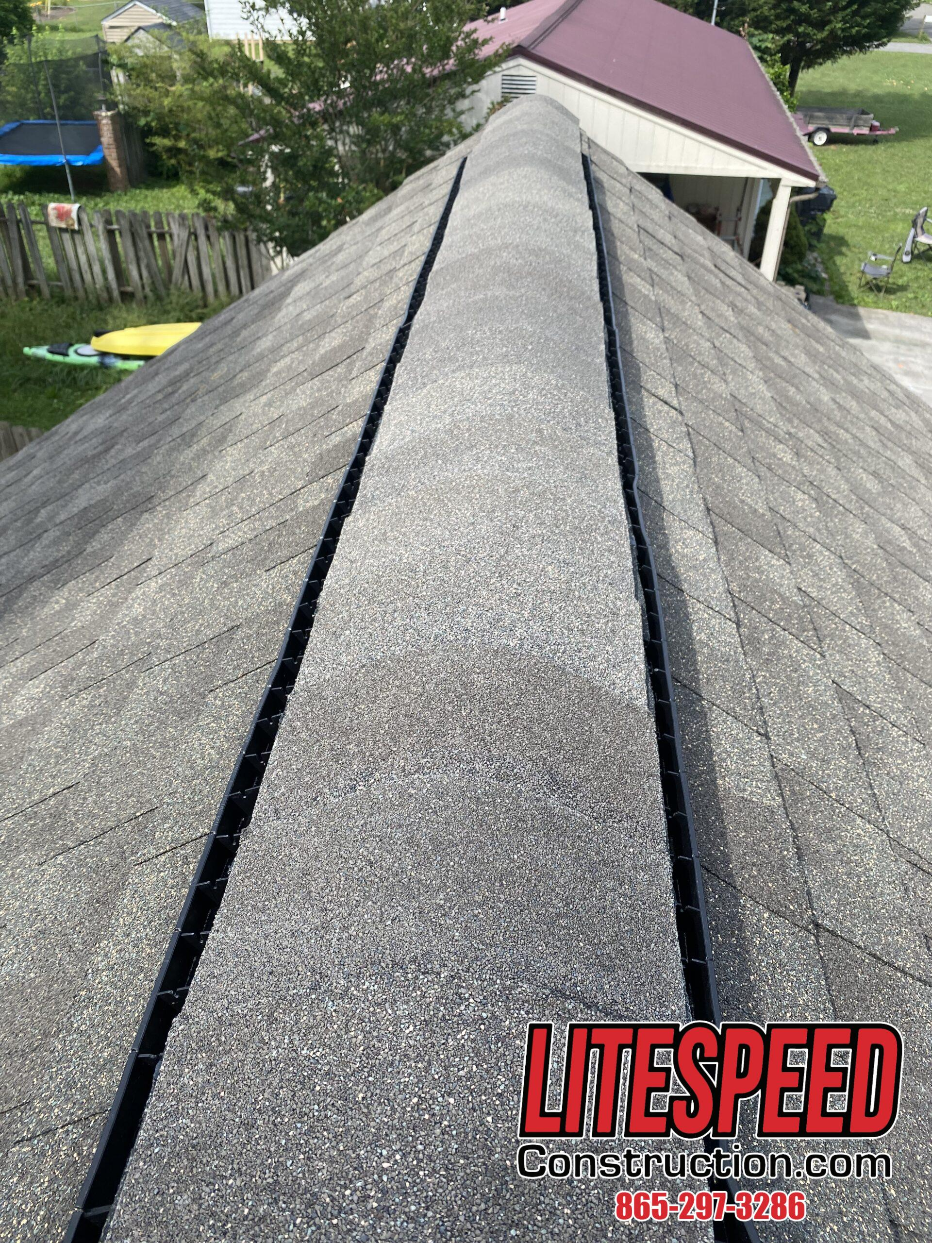 This is a picture of a new black plastic ridge vent with ridge cap shingles