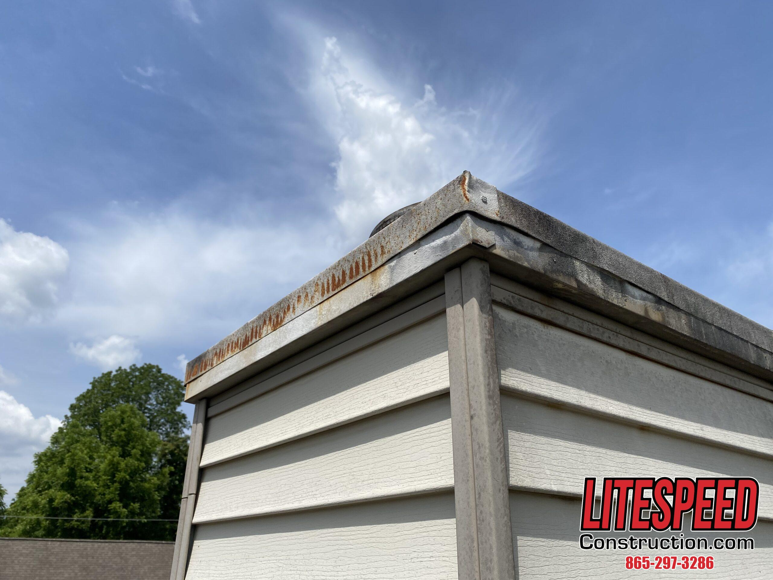 This is a picture of a rusty chimney cap on a steep roof