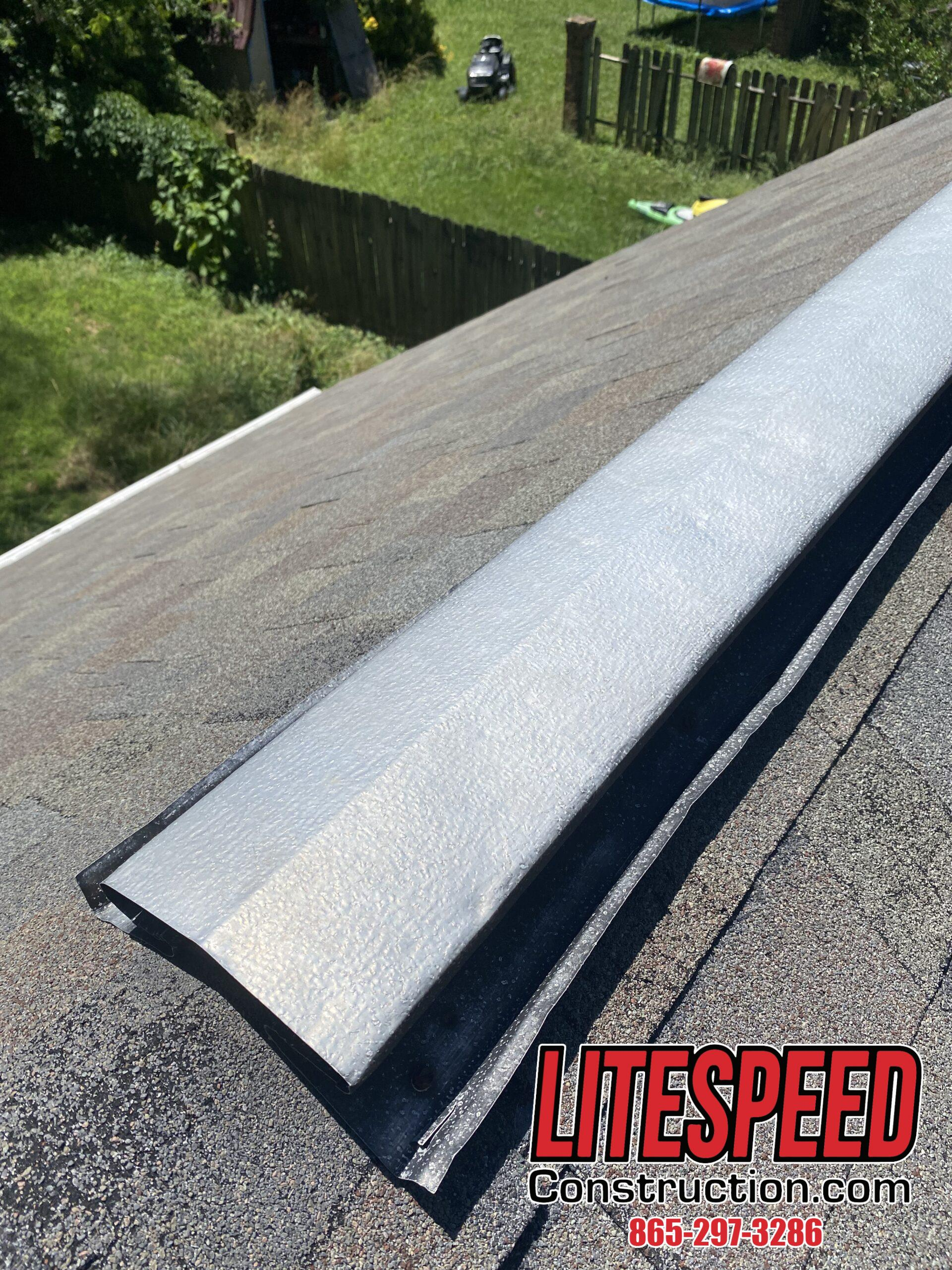 This is a picture of an old black metal ridge vent on a steep roof