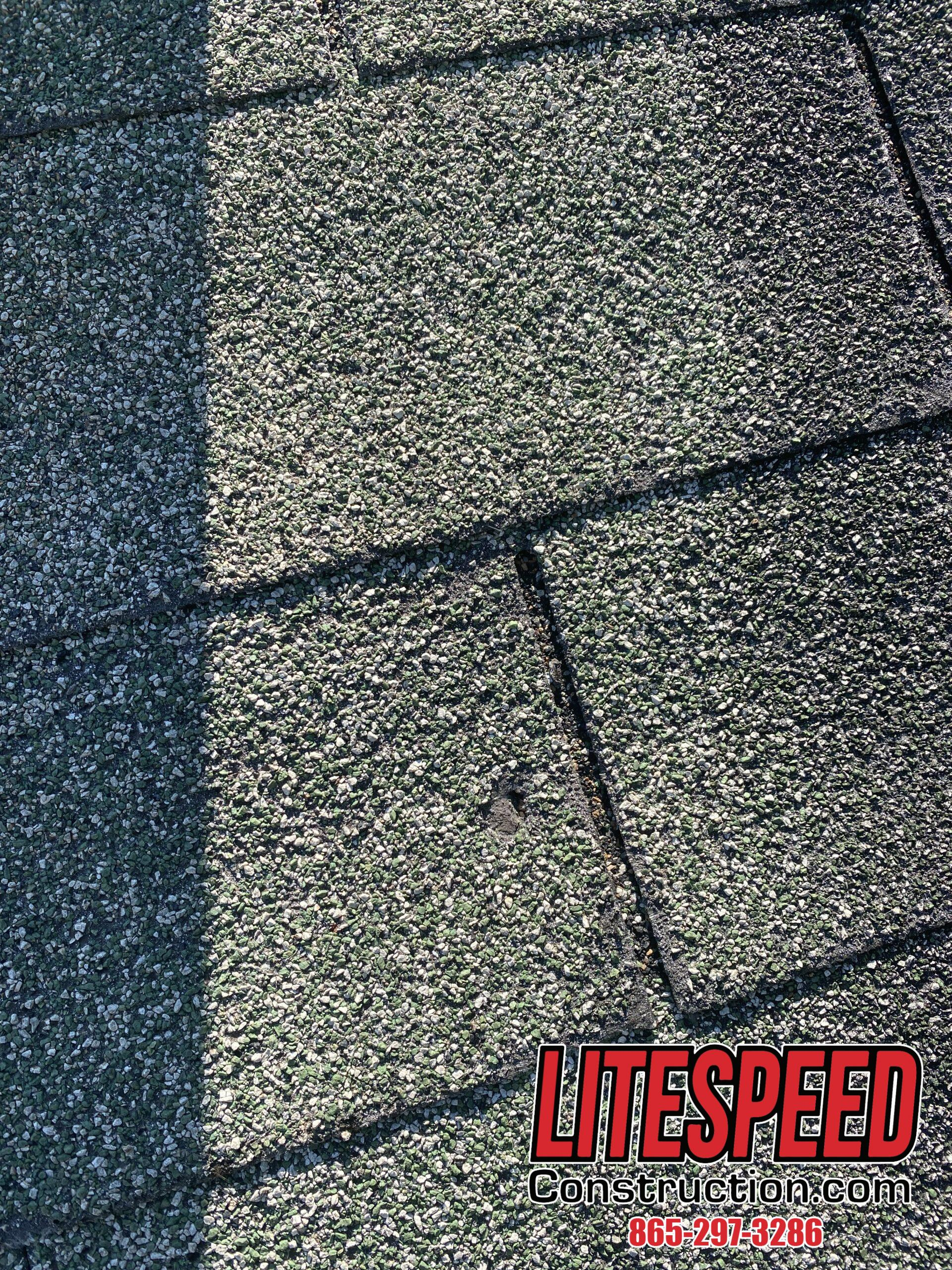 This is a picture of an old three tab roof with a piece of the shingle missing