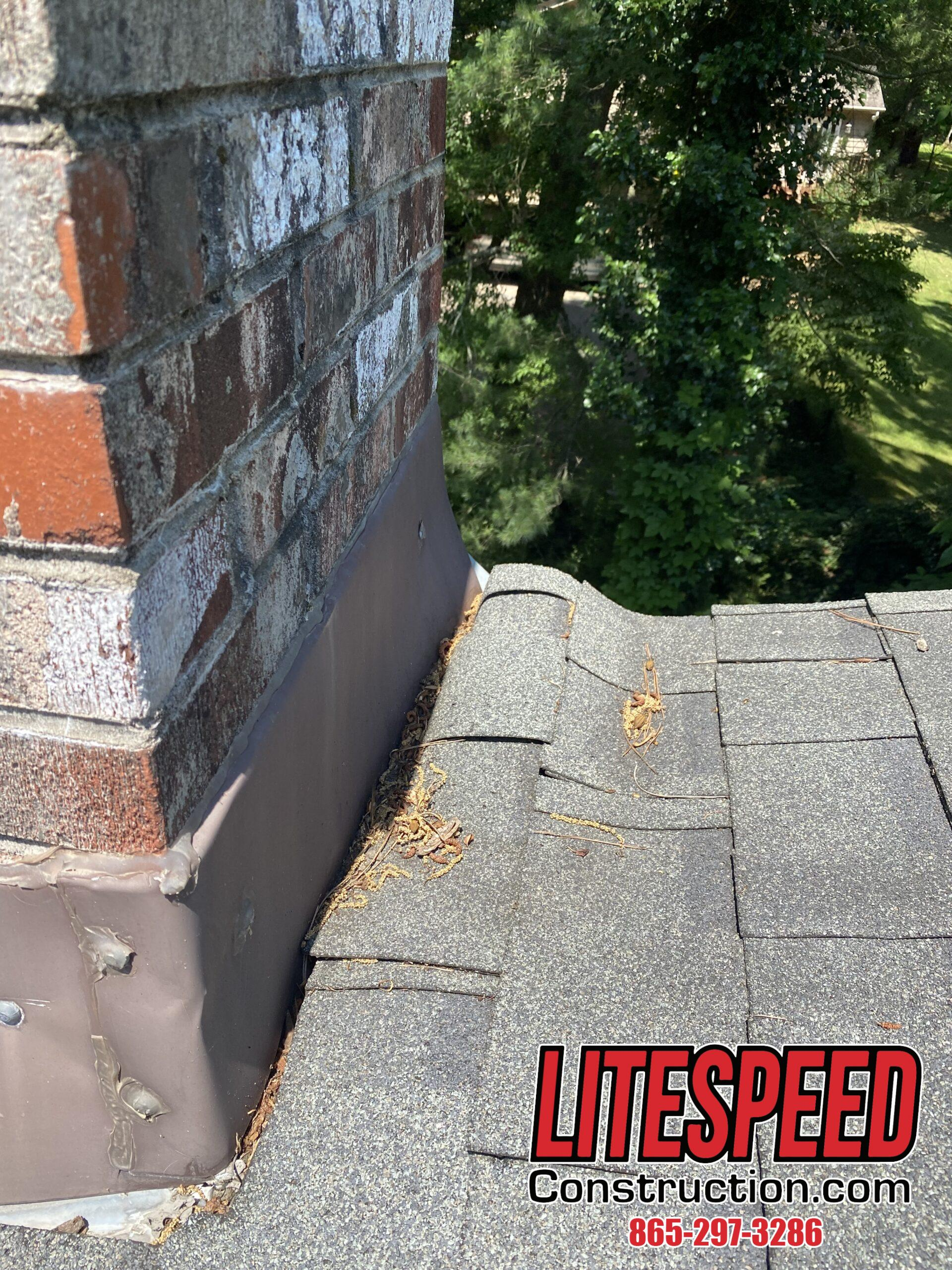 This is a picture of a gray dimensional shingle bunched up at the chimney