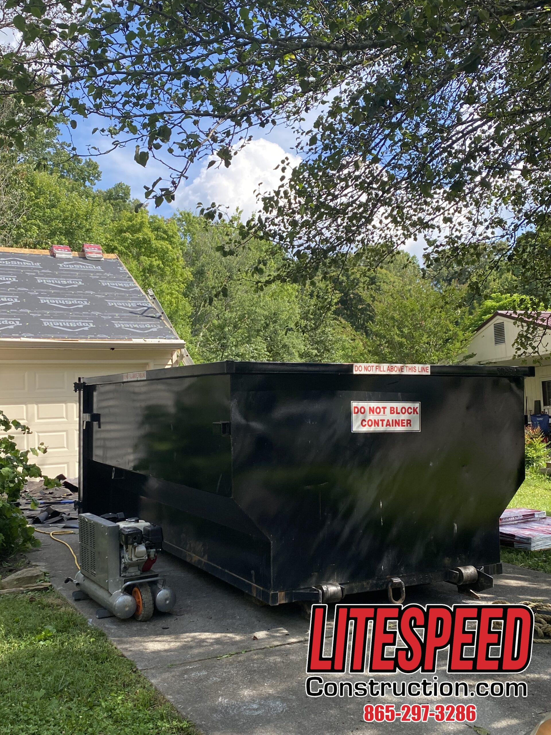 This is a picture of a black dumpster at the driveway of a house