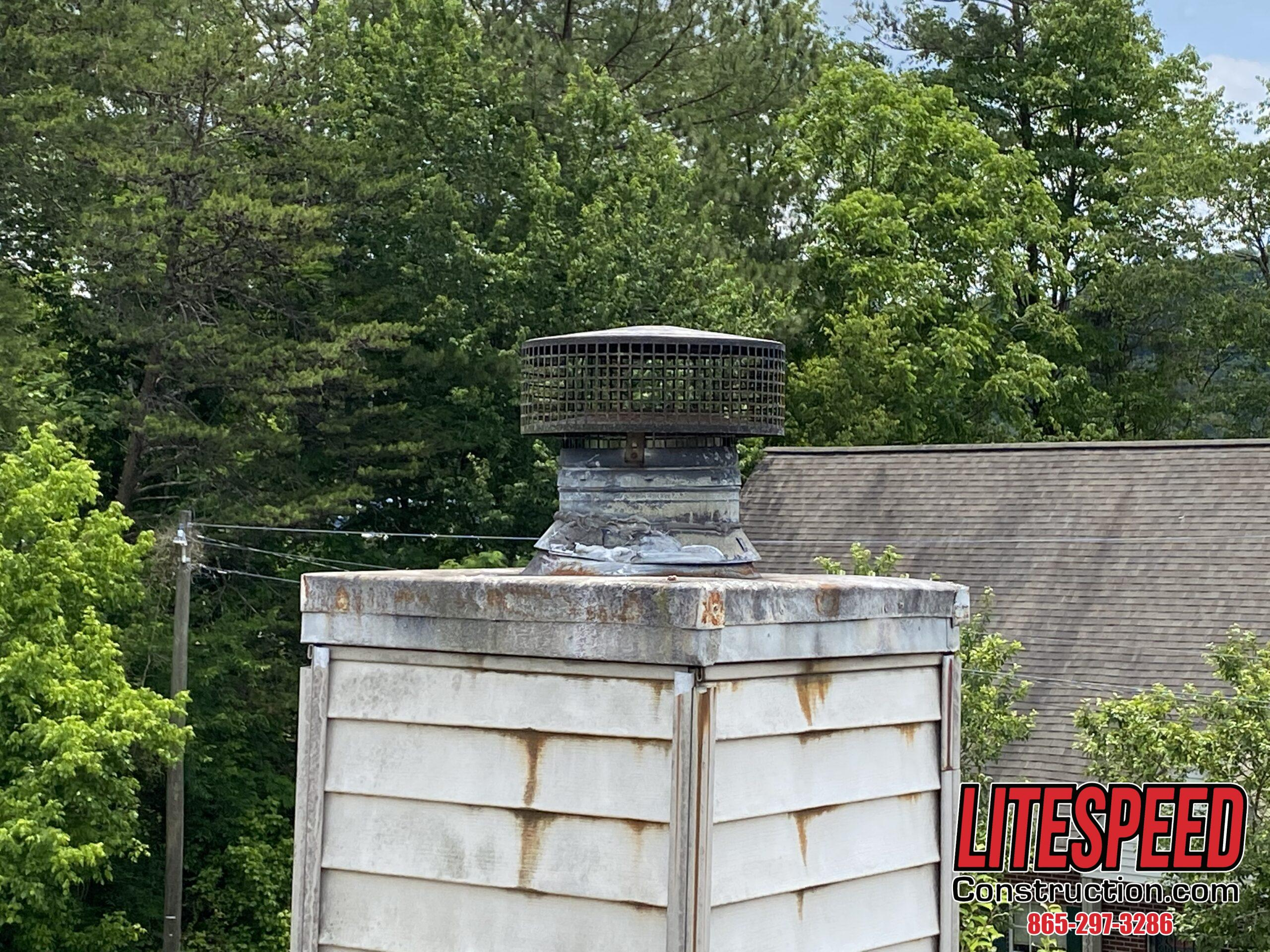 This is a picture of an old rusty chimney cap on a steep roof