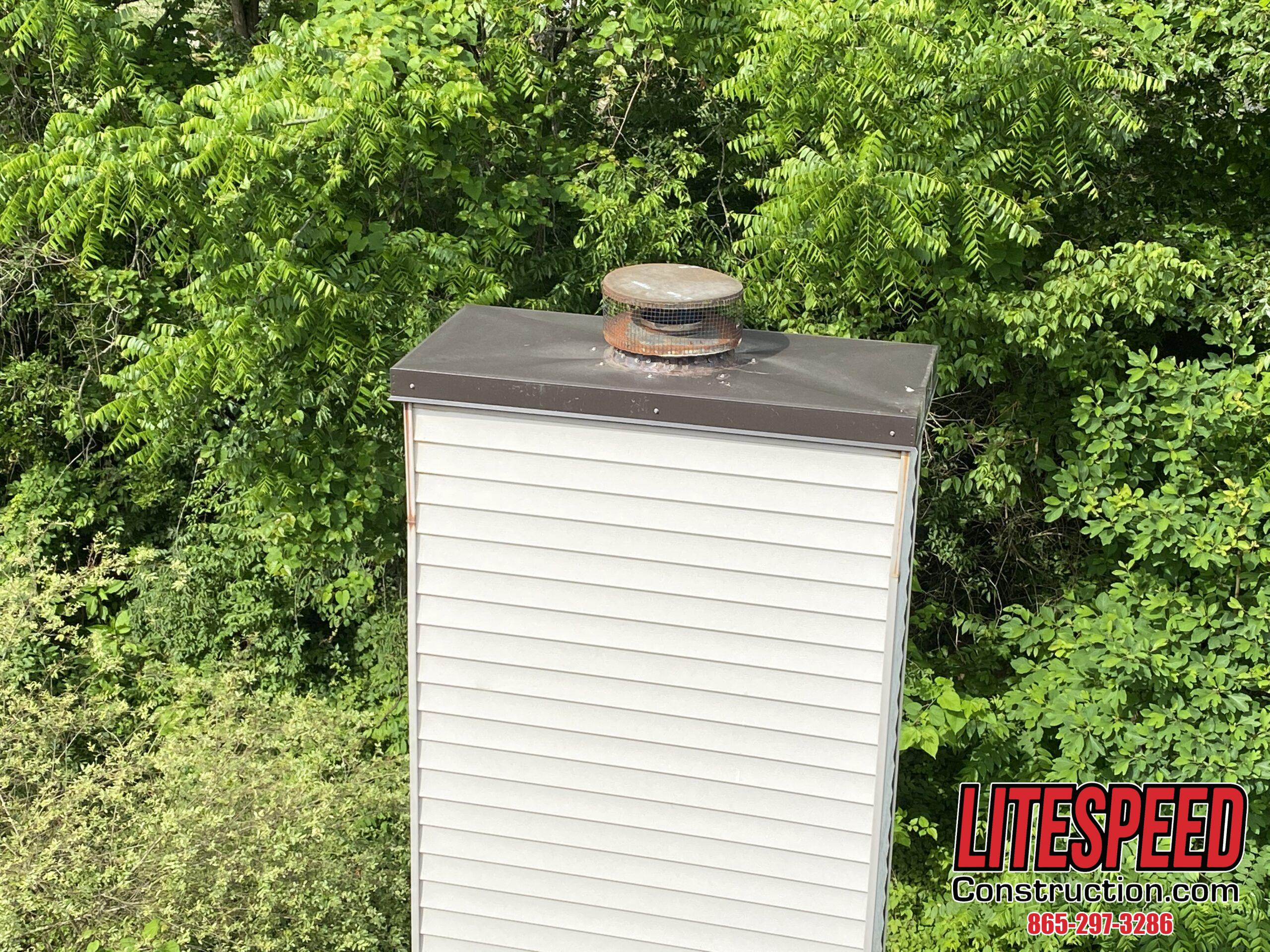 This is a picture of a brand new chimney cap on a steep roof