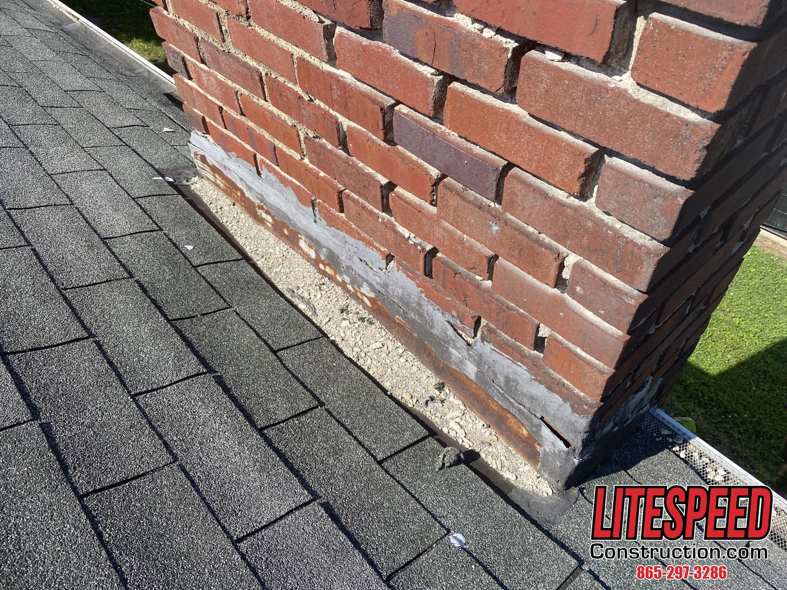 This is a picture of a brick  chimney with bad flashing at the roof