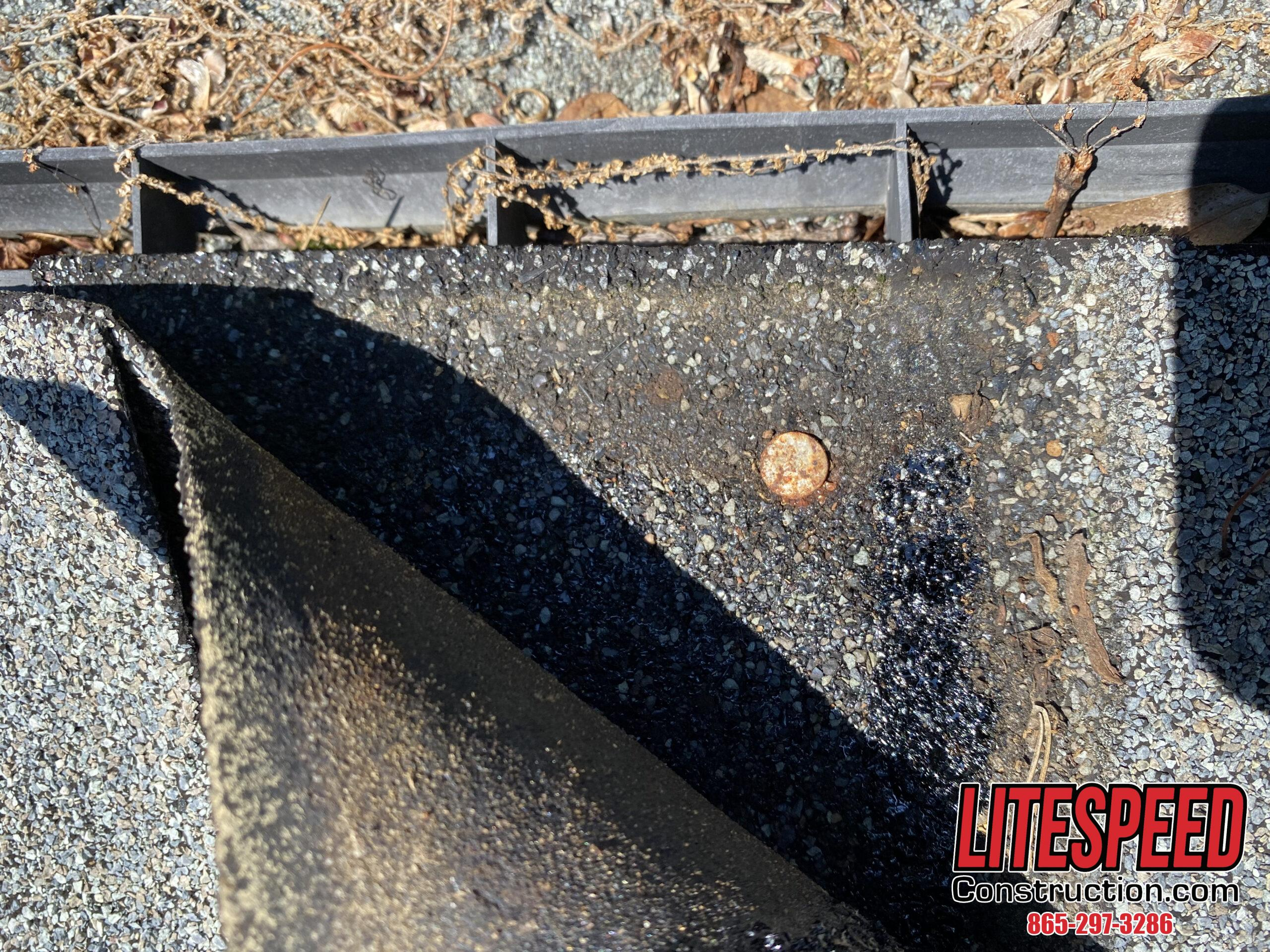 This is a picture of a rusty nail underneath a ridge cap shingle.