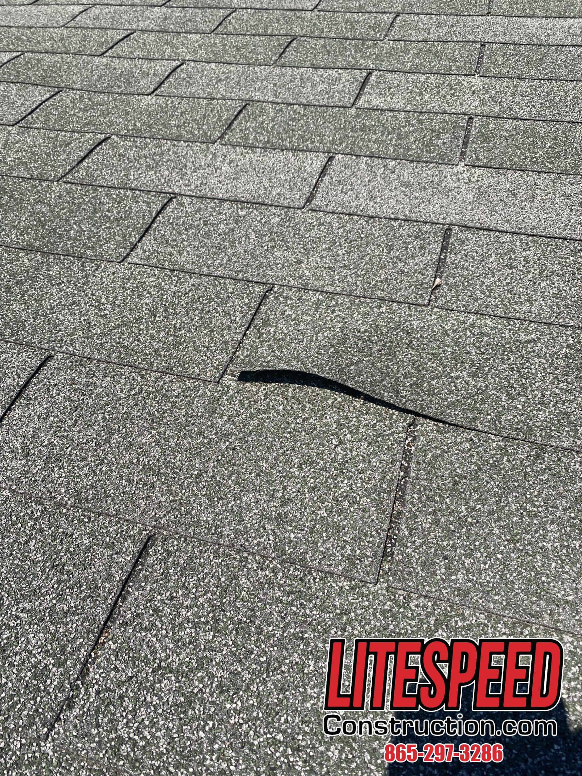 This is a picture of an old three tab roof with a nail pop.
