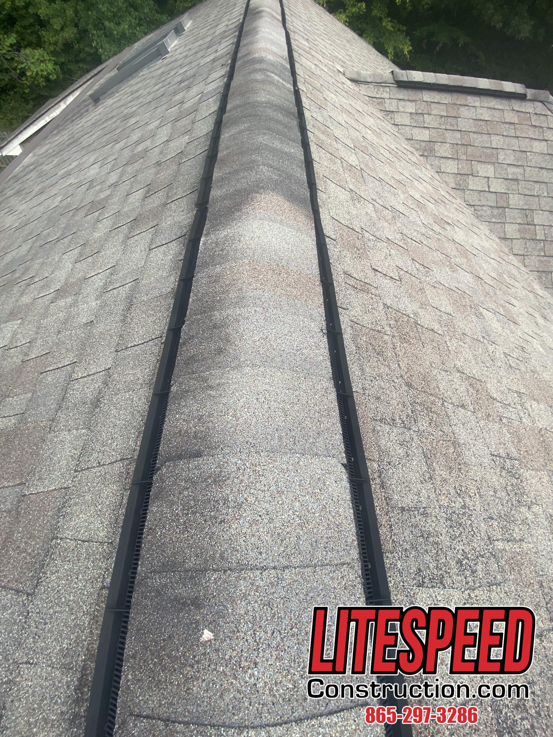 This is a picture of a black plastic ridge vent with shingles over the top