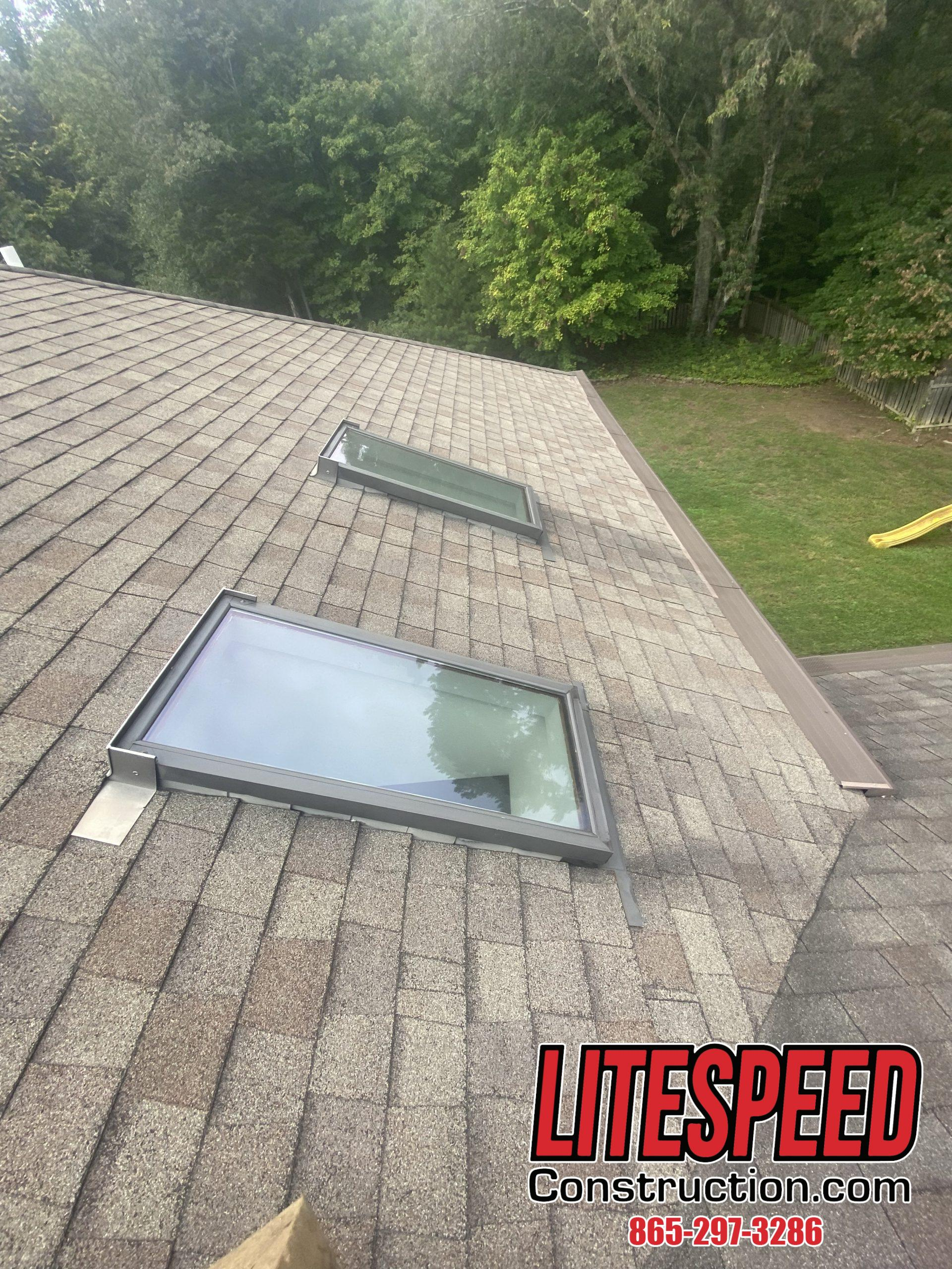 This is a picture of two skylights on a shingle roof