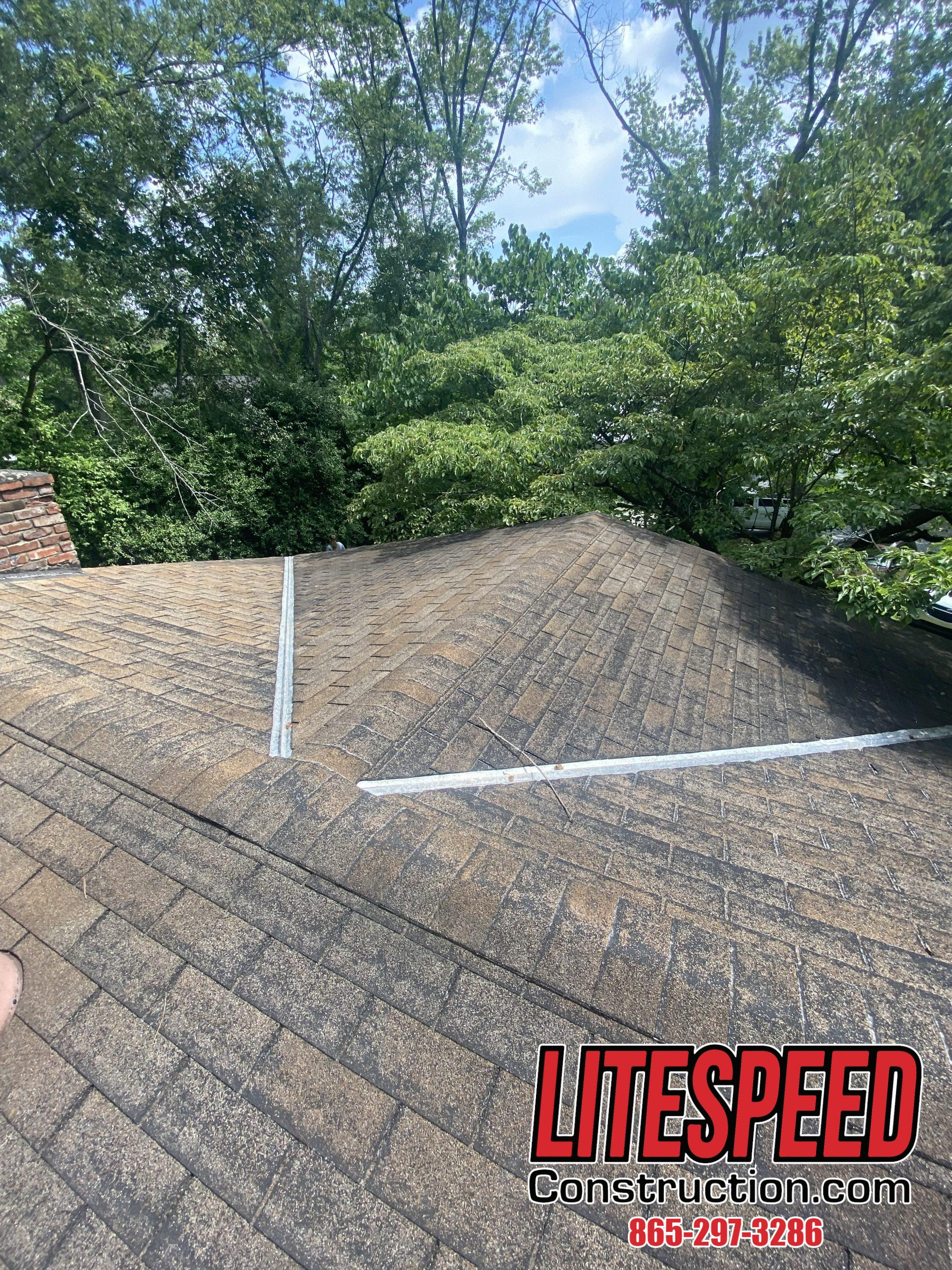 This is a picture of an old three tab roof with metal inside the valleys